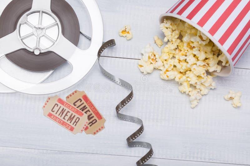 Copo de papel com a pipoca, dispersada ao lado do filme e dos bilhetes para uma sessão do filme imagens de stock