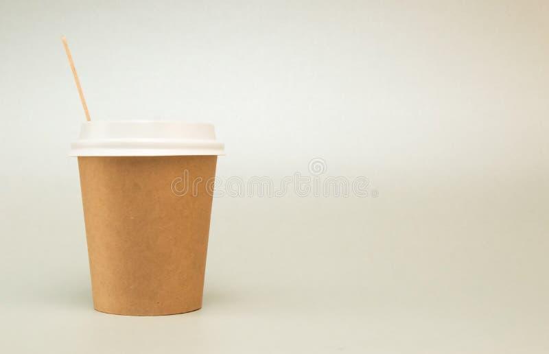 Copo de papel com a tampa para cremalheiras do caf? em um fundo branco, ao lado de uma colher de caf? de madeira fotos de stock