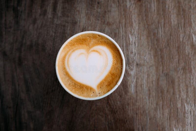 Copo de papel do café do cappuccino com arte bonita do latte na forma do coração no fundo de madeira Vista superior, espa?o da c? fotografia de stock