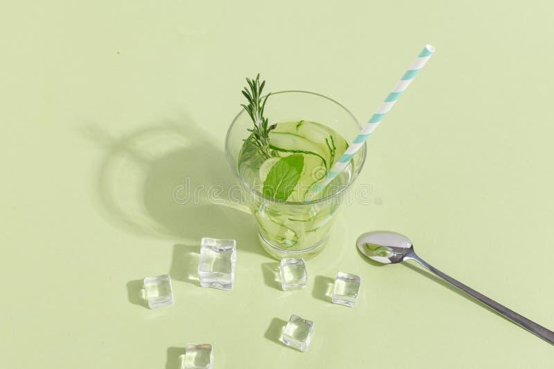 Copo de vidro com água do pepino em um claro - fundo verde Conceito criativo de Minimalistic Copie o espaço fotografia de stock
