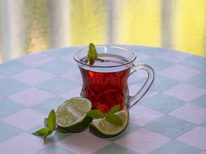 Copo de vidro com chá preto, cal e hortelã em uma tabela de madeira na perspectiva da cor amarela imagens de stock royalty free
