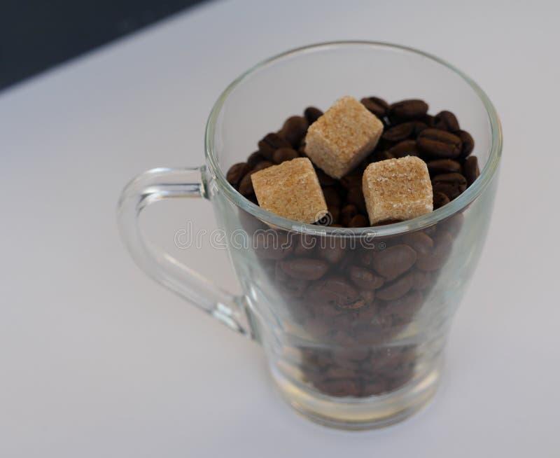 Copo de vidro com os feijões de café com os três cubos do açúcar mascavado foto de stock royalty free
