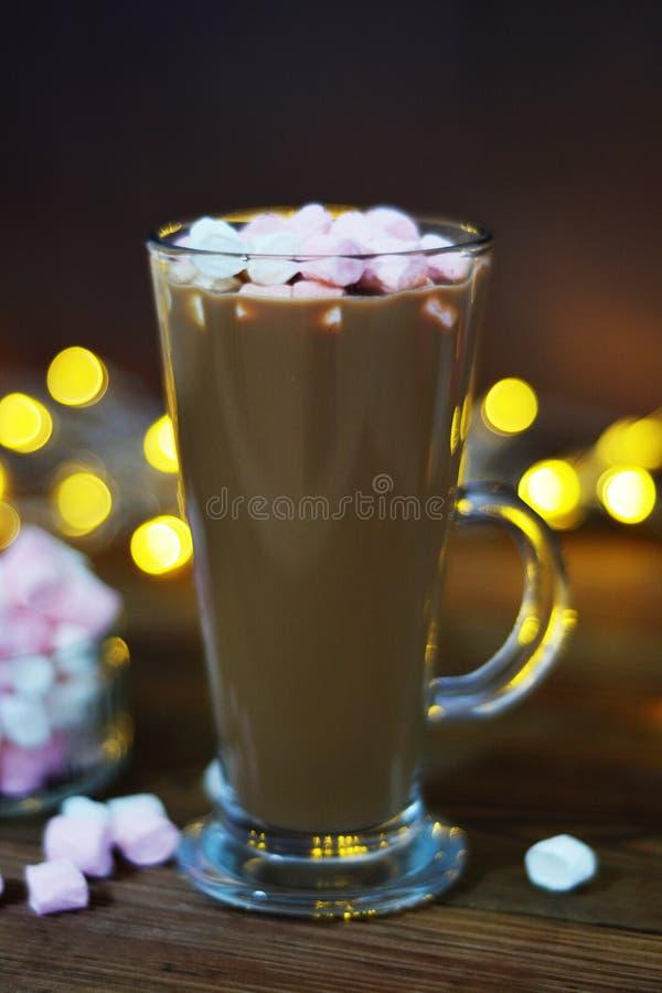 Copo de vidro do cacau com marshmallow em um fundo de madeira com luzes de Natal festivas do bokeh Imagem vertical imagens de stock royalty free