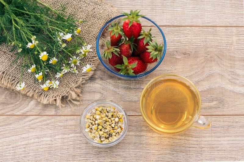 Copo de vidro do chá verde, stawberries com as flores brancas da camomila no fundo de madeira imagens de stock