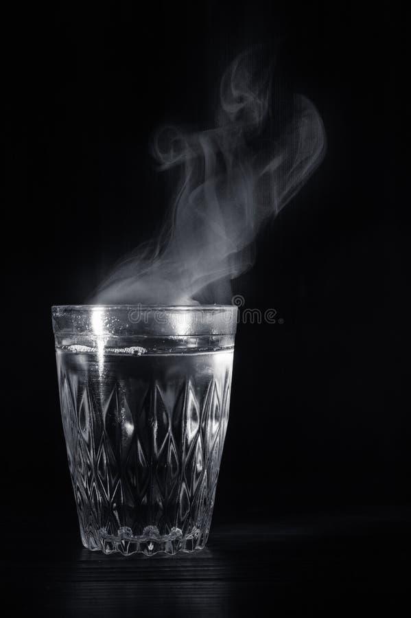 Copo de vidro transparente com inchamento a água a ferver nela O vapor da parte superior Fundo preto fotos de stock