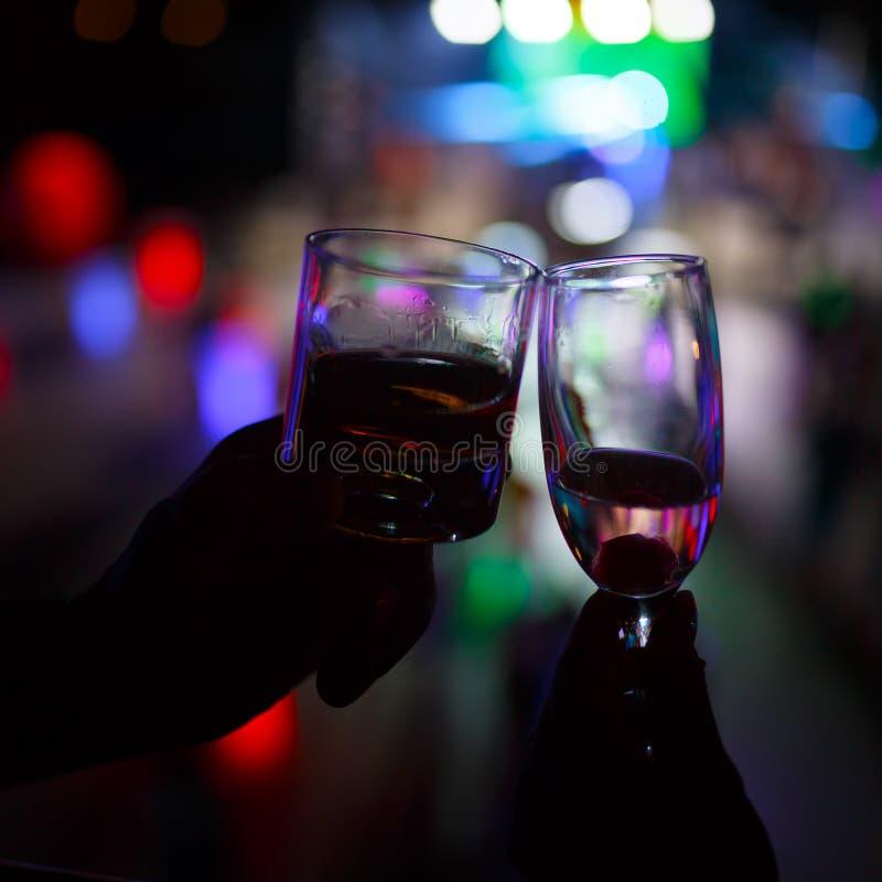 Copo de vinho do champanhe na mão da mulher e em um vidro do uísque em uma mão do homem contra o fundo escuro foto de stock