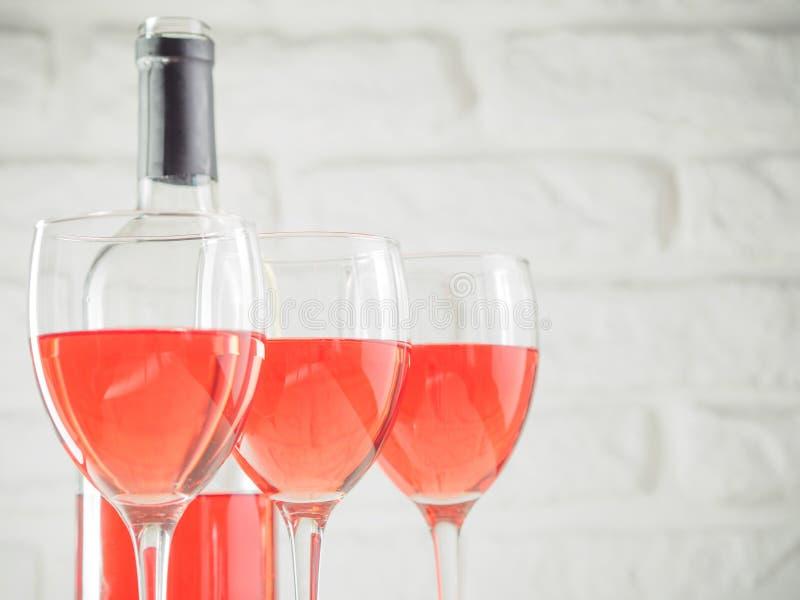 Copo de vinho três com vinho cor-de-rosa e garrafa no fundo branco da parede de tijolo imagem de stock