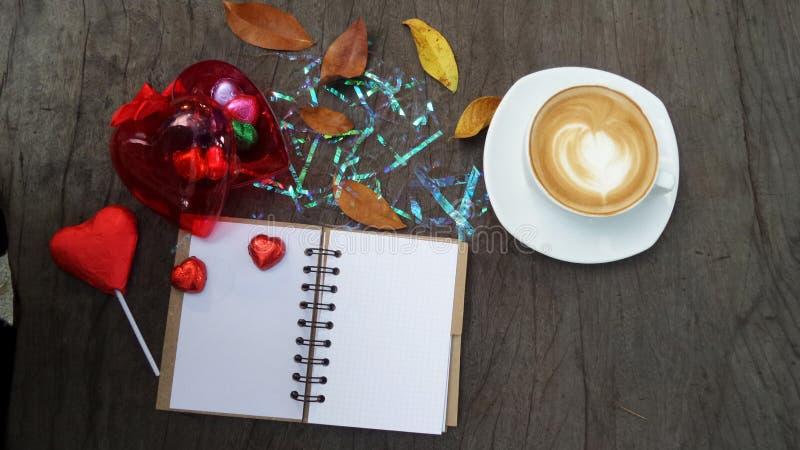 Copo do bloco de notas, do computador e de café na tabela de madeira do escritório, vista superior imagens de stock