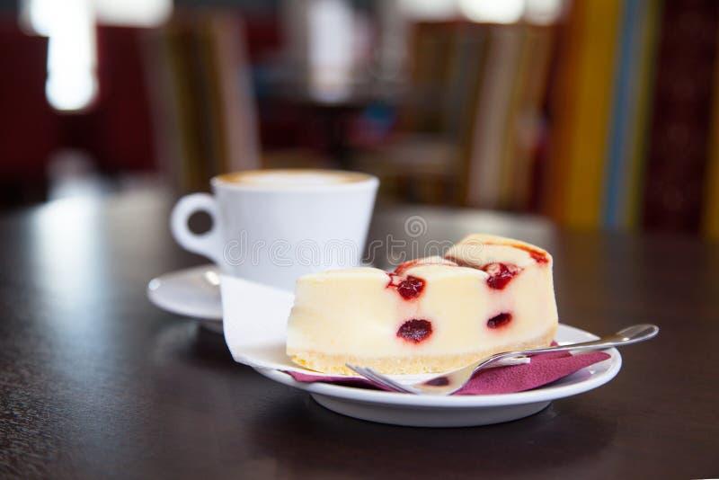 Copo do bolo de queijo e de café em uma tabela em um café fotos de stock