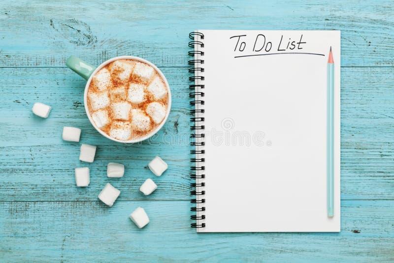 Copo do cacau ou do chocolate quente com o marshmallow e o caderno com para fazer a lista na tabela do vintage de turquesa acima, fotografia de stock