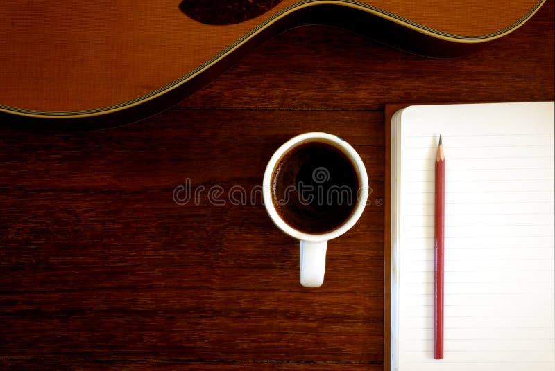 Copo do caderno, do lápis e de café com guitarra acústica imagem de stock royalty free