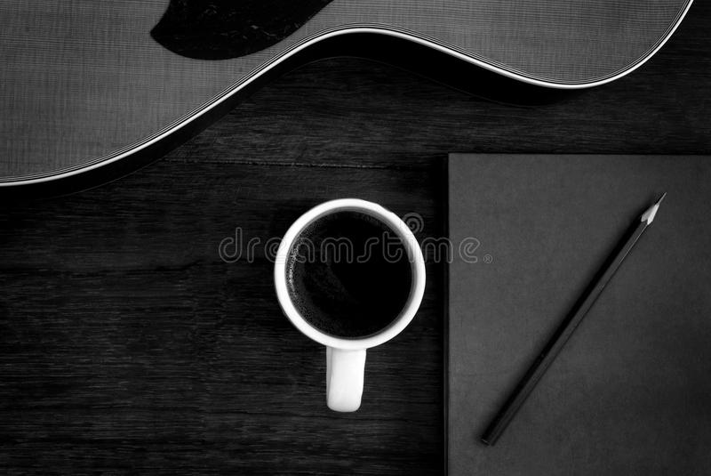 Copo do caderno, do lápis e de café com a guitarra acústica no assoalho de madeira imagem de stock