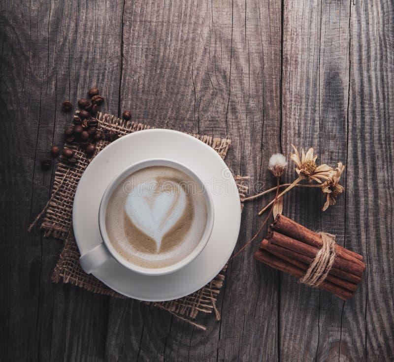 Copo do café do cappuccino na tabela de madeira do vintage velho, flor seca, canela, vista superior fotos de stock