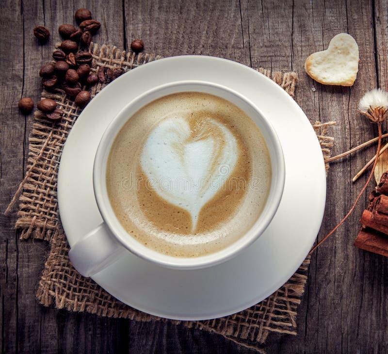 Copo do café do cappuccino na tabela de madeira do vintage velho, flor seca, canela, vista superior imagens de stock royalty free