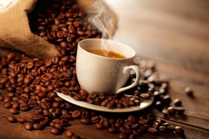 Copo do café com os feijões do saco e de café da juta imagem de stock