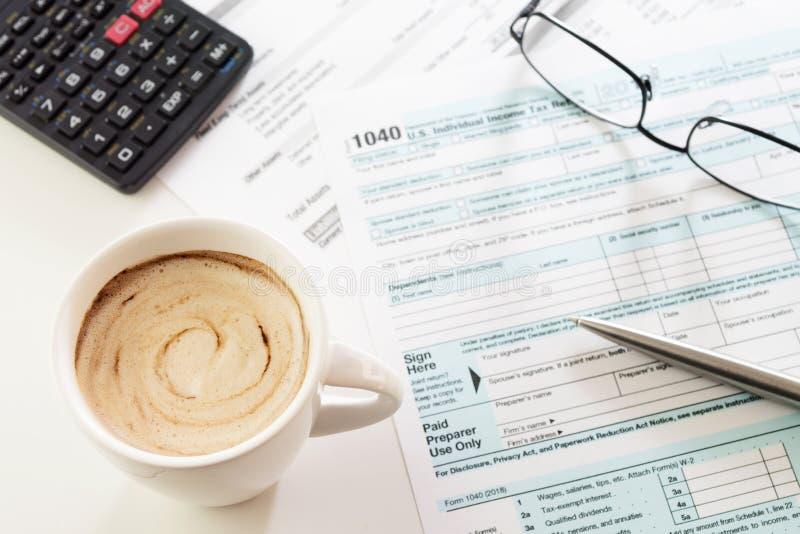 Copo do café cremoso com formulário de declaração de rendimentos, pena, calculadora e vidros na tabela fotos de stock