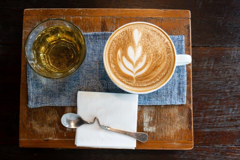 Copo do café da arte do latte e do chá quente fotografia de stock