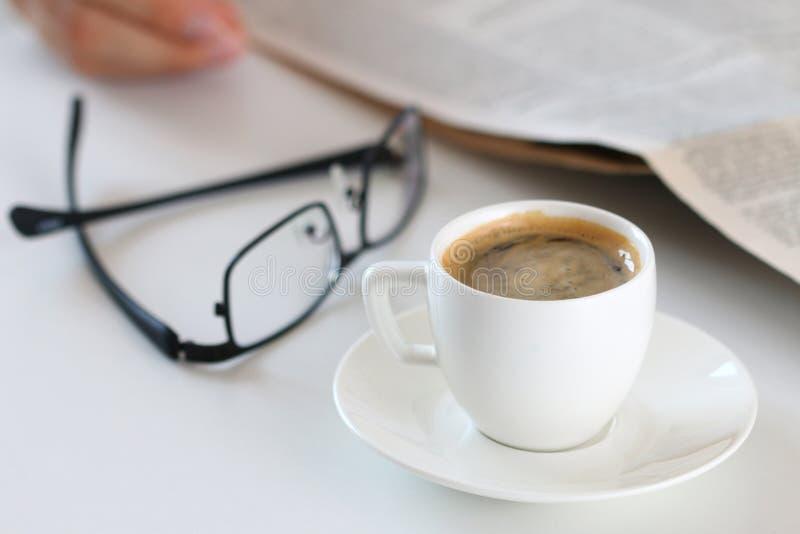 Copo do café da manhã no worktable com vidros e jornal fotografia de stock