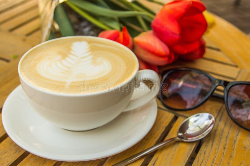 Copo do café, de vidros e de tulipas quentes da arte do latte na tabela de madeira fotografia de stock royalty free