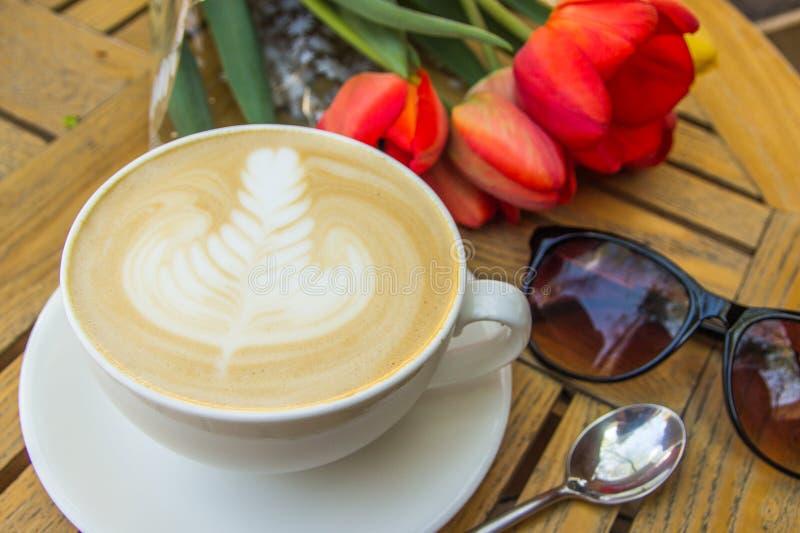 Copo do café, de vidros e de tulipas quentes da arte do latte na tabela de madeira fotografia de stock