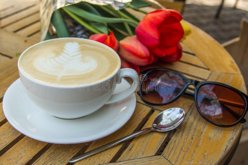 Copo do café, de vidros e de tulipas quentes da arte do latte na tabela de madeira imagens de stock