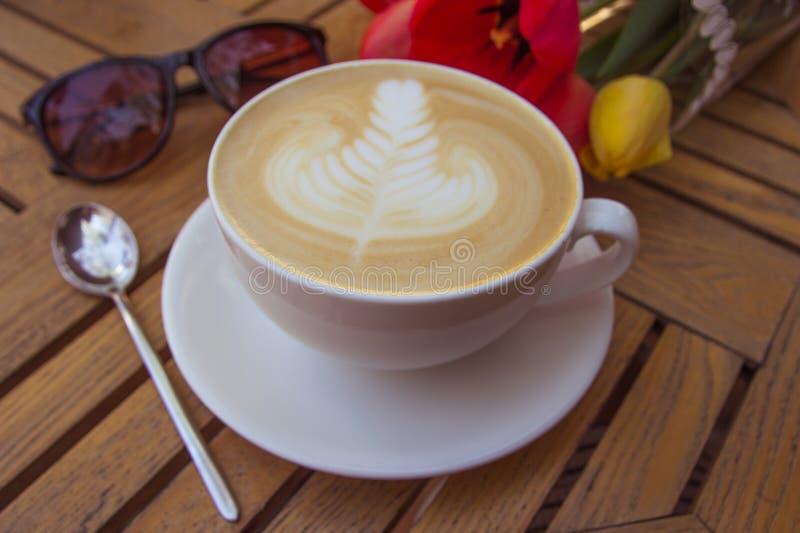Copo do café, de vidros e de tulipas quentes da arte do latte na tabela de madeira fotos de stock royalty free