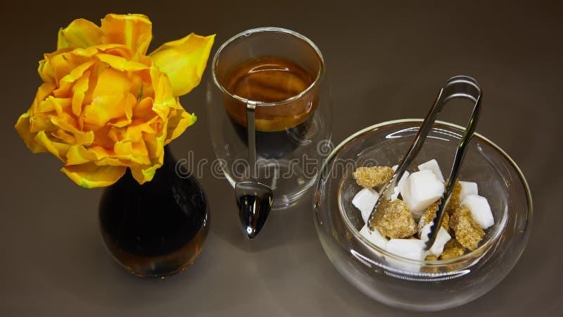 Copo do café do café, do açúcar e da tulipa amarela fotografia de stock
