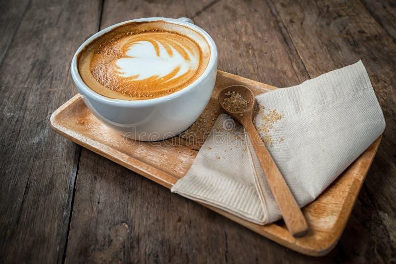 Copo do café do cappuccino na placa e no açúcar mascavado de madeira foto de stock royalty free