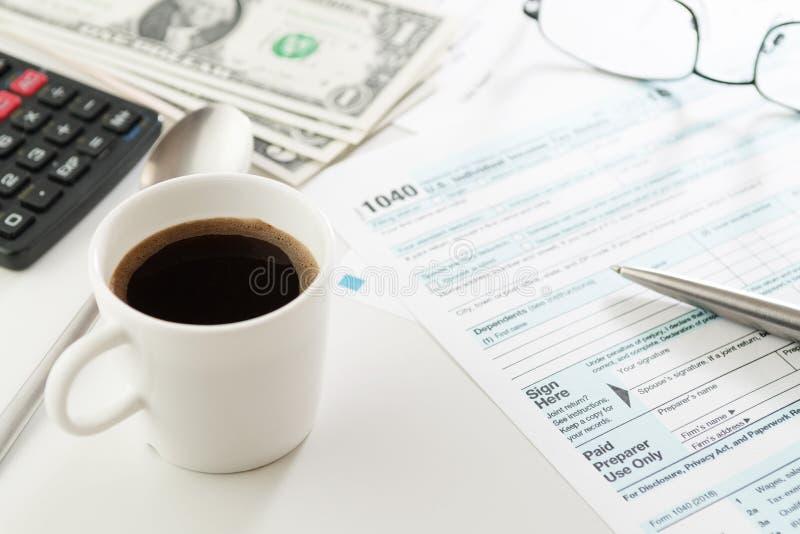 Copo do café e do formulário de declaração de rendimentos da renda com dinheiro, calculadora e vidros imagem de stock