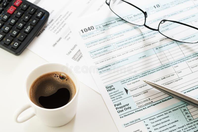 Copo do café, formulário de declaração de rendimentos da renda com calculadora, vidros e pena na tabela foto de stock