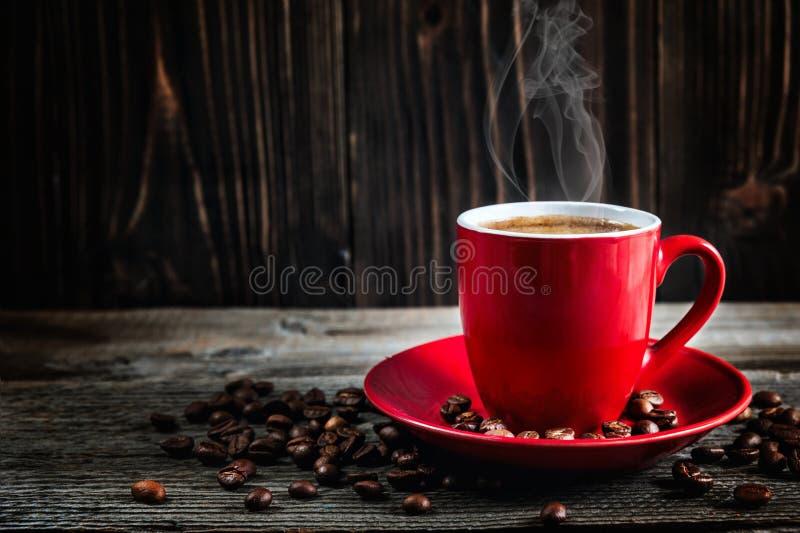 Copo do café fresco com os feijões de café na tabela de madeira imagem de stock royalty free