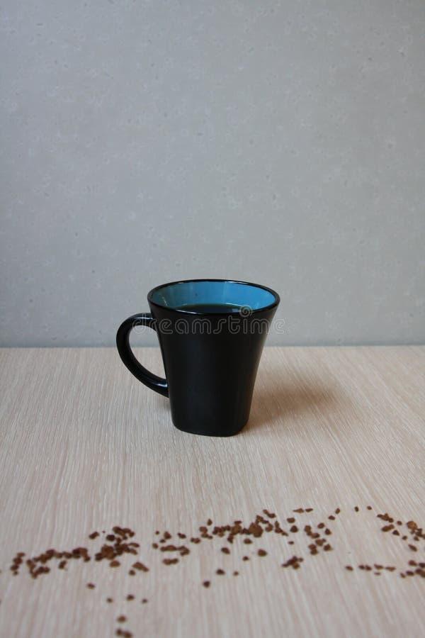 Copo do café fresco no fundo claro com café do pó da grão fotografia de stock royalty free