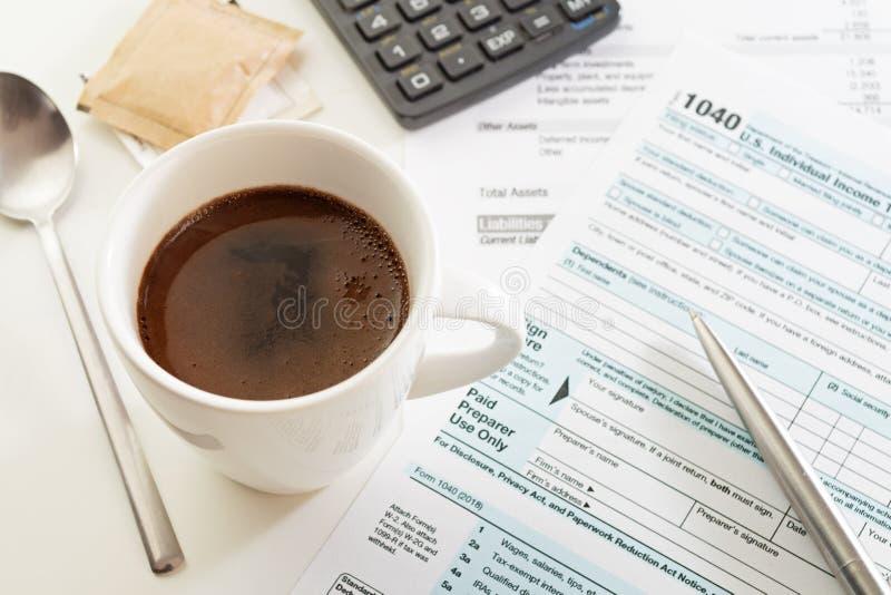 Copo do café na tabela branca com formulário, pena e calculadora de declaração de rendimentos da renda foto de stock royalty free
