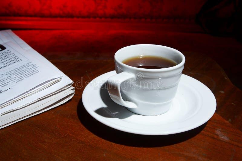 Copo do café perfumado em um negócio do papel de manhã fotos de stock