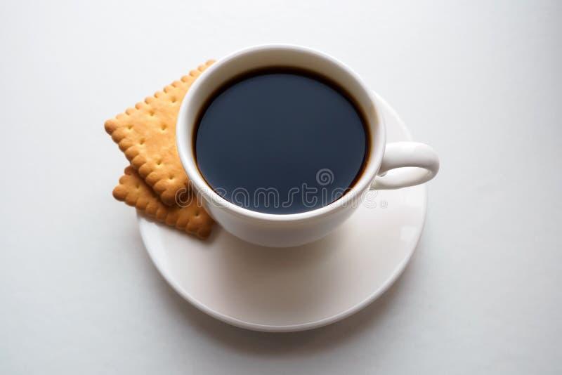 Copo do café preto com os biscoitos em pires no fundo branco fotos de stock royalty free