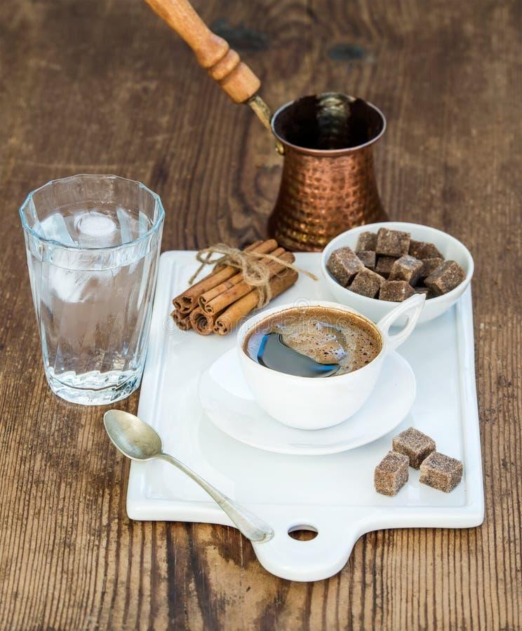 Copo do café preto, do potenciômetro de cobre, da água com gelo no vidro, das varas de canela e dos cubos do açúcar de bastão no  fotos de stock