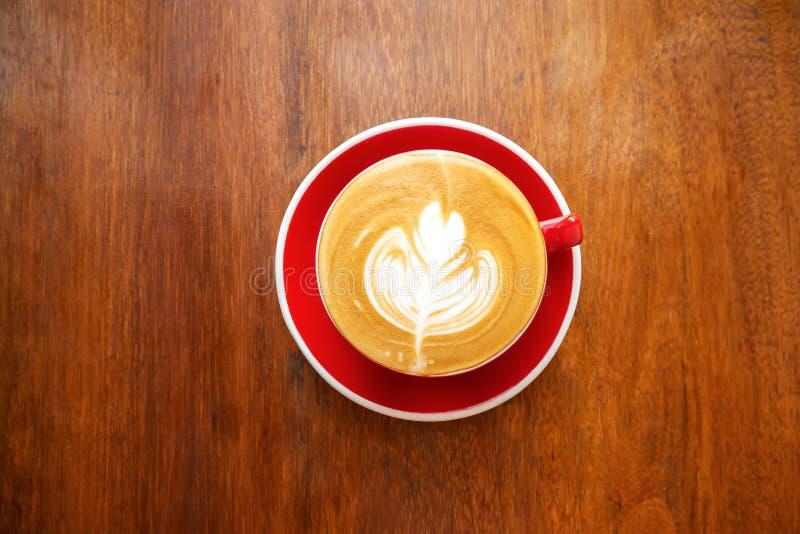 Copo do café quente com arte do latte na forma de folha na tabela de madeira Vista superior foto de stock
