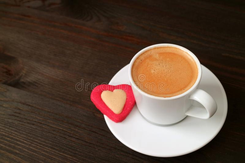 Copo do café quente com uma cookie dada forma coração na tabela de madeira marrom escura imagens de stock royalty free