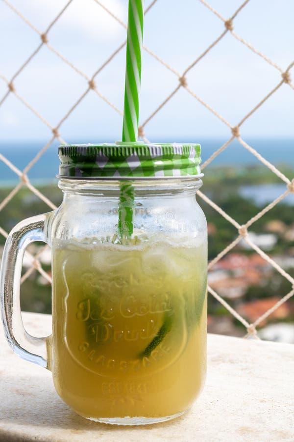 Copo do caipirinha brasileiro da bebida com a praia no fundo fotografia de stock royalty free