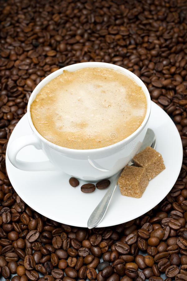 Copo do cappuccino com açúcar mascavado em feijões de café imagem de stock