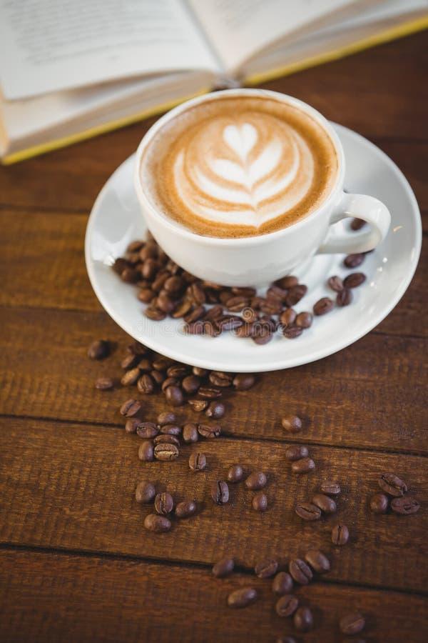 Copo do cappuccino com arte do café e feijões de café fotos de stock royalty free