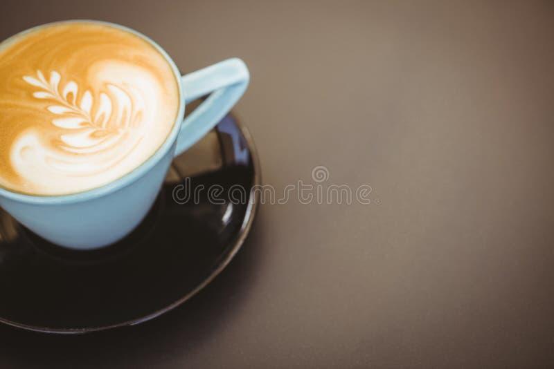 Copo do cappuccino com arte do café na tabela de madeira foto de stock