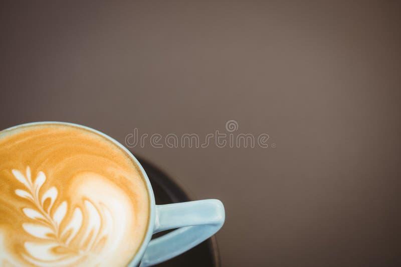 Copo do cappuccino com arte do café na tabela de madeira imagem de stock