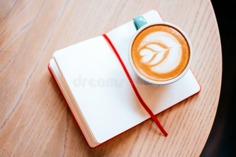 Copo do cappuccino com caderno imagem de stock royalty free