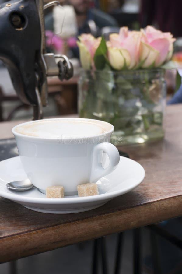Copo do cappuccino com os cubos do açúcar mascavado na cafetaria imagens de stock royalty free