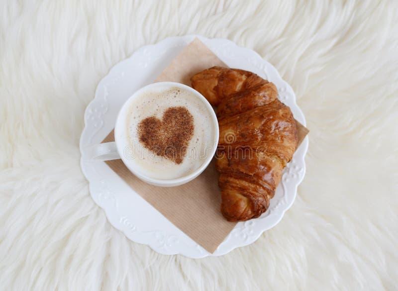 Copo do cappuccino com teste padrão do coração da canela e do croissant imagem de stock