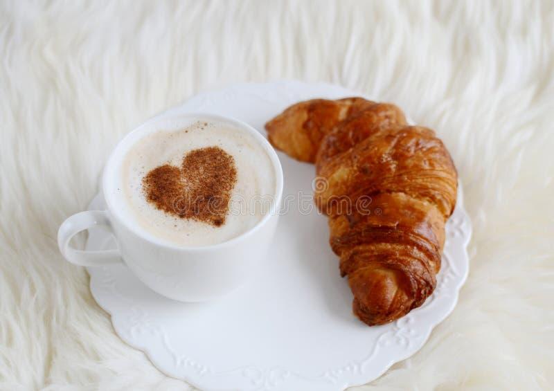 Copo do cappuccino com teste padrão do coração da canela e do croissant fotografia de stock royalty free