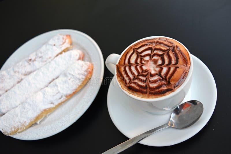 Copo do cappuccino e da sobremesa espumosos deliciosos em uma tabela preta imagem de stock