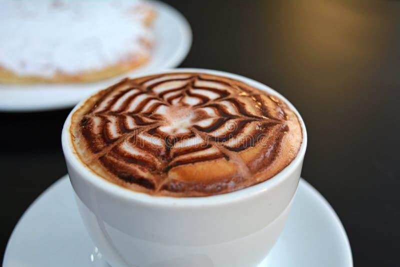 Copo do cappuccino e da sobremesa espumosos deliciosos em uma tabela preta foto de stock