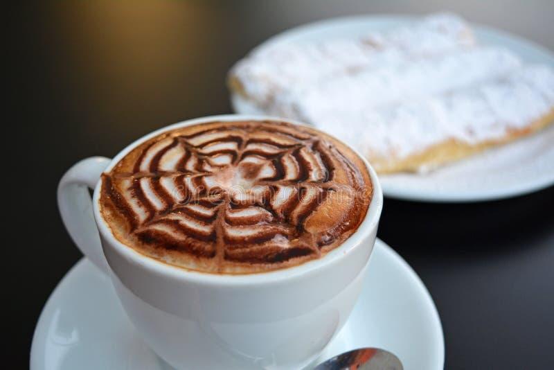 Copo do cappuccino e da sobremesa espumosos deliciosos em uma tabela preta imagem de stock royalty free